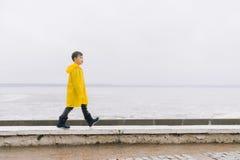 Een jongen in een gele mantelregenjas loopt langs de kust G royalty-vrije stock afbeeldingen