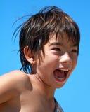 Een jongen gilt en glimlacht Stock Foto's