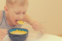 Een jongen in een grijze T-shirt heeft een ontbijt van cornflakes met melk stock foto's