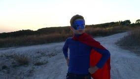 Een jongen kleedde zich omhoog met een Kaap van Superman die zich op een berg bevinden de zonsondergang bekijken stock video