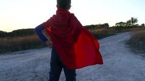 Een jongen kleedde zich omhoog met een Kaap van Superman die zich op een berg bevinden de zonsondergang bekijken stock videobeelden
