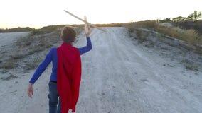 Een jongen kleedde zich omhoog met een Kaap van Superman die zich op een berg bevinden de zonsondergang bekijken stock footage