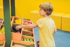 Een jongen koopt stuk speelgoed groenten in een stuk speelgoed supermarkt stock afbeeldingen