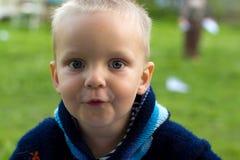 Een jongen met blauwe ogen en blond haar glimlacht bij de camera Stock Afbeeldingen