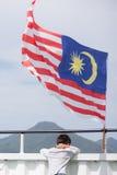 een jongen met de fladderende vlag van Maleisië Stock Afbeeldingen