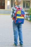 Een jongen met een knapzak, boeken en een bol gaat naar school na de lange zomer royalty-vrije stock afbeeldingen
