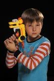 Een jongen met een stuk speelgoed kanon. Royalty-vrije Stock Afbeeldingen