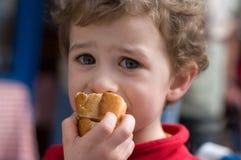 Een jongen met een stuk van brood stock foto's