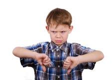 Een jongen met een emotie van ontevredenheid en gebaarafkeer isoleer stock foto's