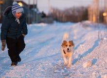 Een jongen met een hond in de stralen van een zonsondergang op de sneeuw stock fotografie