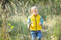 Een jongen met een houten stok stock afbeelding