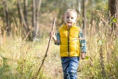 Een jongen met een houten stok stock foto's