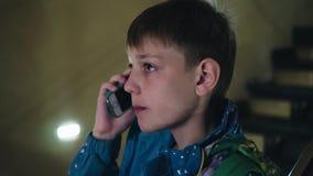 Een jongen met een nadenkende blik luistert aan wat hij op de telefoon wordt verteld Sluit omhoog Kinderen` s emoties stock footage