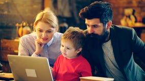 Een jongen met ouders is geinteresseerd in het letten van een op video op laptop Het leren concept Ouders en zoon die thuis ontsp stock videobeelden