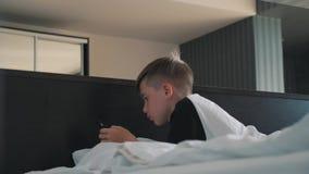 Een jongen met een smartphone ligt op het bed De jongen communiceert met vrienden met behulp van een smartphone stock videobeelden