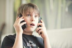 Een jongen met telefoons stock afbeelding