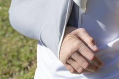 Een jongen met verwond dient een het bevestigen verband op de achtergrond van een voetbalgebied in stock foto