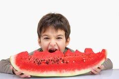 Een jongen met watermeloen stock afbeeldingen