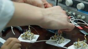 Een jongen met een witte laag werkt in het wetenschappelijke laboratorium Close-up van een hand stock video