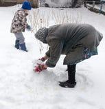 Een jongen met zijn grootmoeder die in de sneeuw spelen royalty-vrije stock foto's