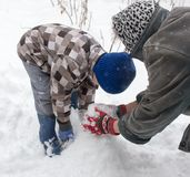 Een jongen met zijn grootmoeder die in de sneeuw spelen stock afbeeldingen
