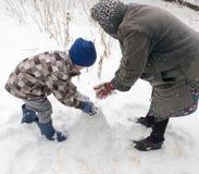 Een jongen met zijn grootmoeder die in de sneeuw spelen stock foto