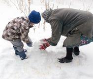 Een jongen met zijn grootmoeder die in de sneeuw spelen stock afbeelding