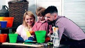 Een jongen met zijn ouders plant bloemen in potten De moeder en de vader onderwijzen jongen om bloemen te planten Het concept het stock footage