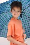 Een jongen onder een open paraplu Stock Afbeeldingen