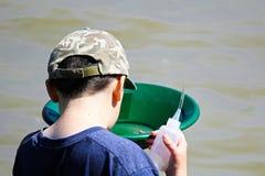 Een jongen onderzoekt een gouden pan ter beschikking met een zuigingsfles royalty-vrije stock fotografie