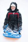 Een jongen op een slee Stock Fotografie