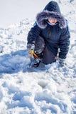 Een jongen op ijs vist in de winter stock afbeeldingen
