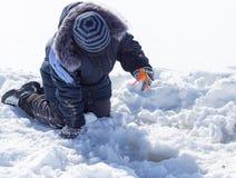 Een jongen op ijs vist in de winter stock foto