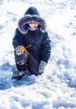Een jongen op ijs vist in de winter stock afbeelding