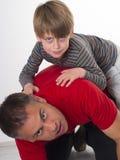 Een jongen op zijn vaders achter, ouderschap kan diffic zijn Royalty-vrije Stock Foto's