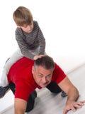 Een jongen op zijn vaders achter, ouderschap kan diffic zijn Royalty-vrije Stock Foto