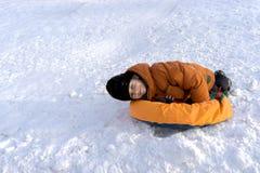 Een jongen in een oranje jasje en een zwarte hoed op een Zonnige de winterdag met een sneeuw glijden op een speciaal broodje en l stock foto