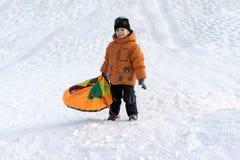 Een jongen in een oranje jasje en een zwarte hoed op een Zonnige de winterdag met een sneeuw glijden op een speciaal broodje en l royalty-vrije stock fotografie