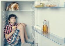 Een jongen in een overhemd en borrels met rode kat die elkaar binnen een koelkast met voedsel en product bekijken Close-up stock afbeelding
