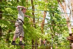 Een jongen overwint hindernissen, lopend op een kabel stock afbeeldingen