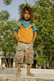 Een jongen in pantoffels die zich op een kleine muur bevinden Stock Afbeelding