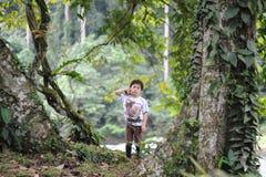 Een jongen playng in een tropisch bos in de Valleireserve van Borneo Danum Stock Foto's