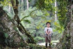 Een jongen playng in een tropisch bos in de Valleireserve van Borneo Danum Stock Afbeeldingen