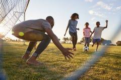 Een jongen schopt een voetbal tijdens een spel met zijn familie royalty-vrije stock afbeeldingen