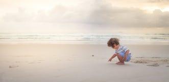 een jongen schrijft op wit zandstrand royalty-vrije stock afbeelding
