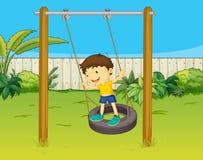 Een jongen slingert op een wiel Stock Fotografie