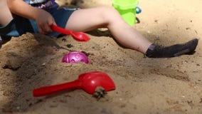 Een jongen speelt in de zandbak stock footage