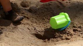 Een jongen speelt in de zandbak stock videobeelden