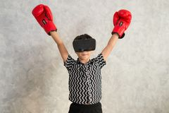 Een jongen speelt in dozen doend spel met 3D virtuele werkelijkheidshoofdtelefoon Royalty-vrije Stock Foto