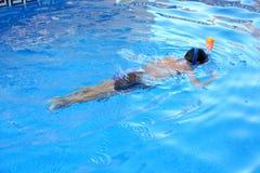 Een jongen speelt in een zwembad met Easybreath-masker Stock Foto